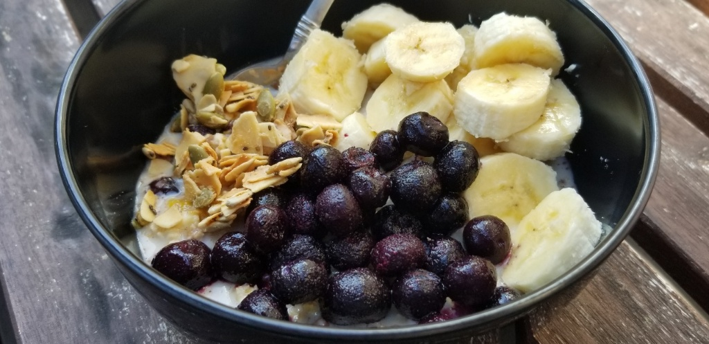image: a bowl of overnight coconut oats topped with sliced banana, frozen blueberries, and oat-and-seed crunch